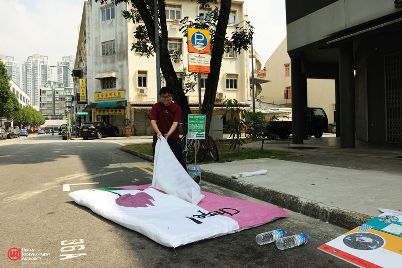 A SUTD student brings a uniquely Singaporean tradition to the road – reserving a space with a tissue packet during PARK(ing) Day 2014. | URA